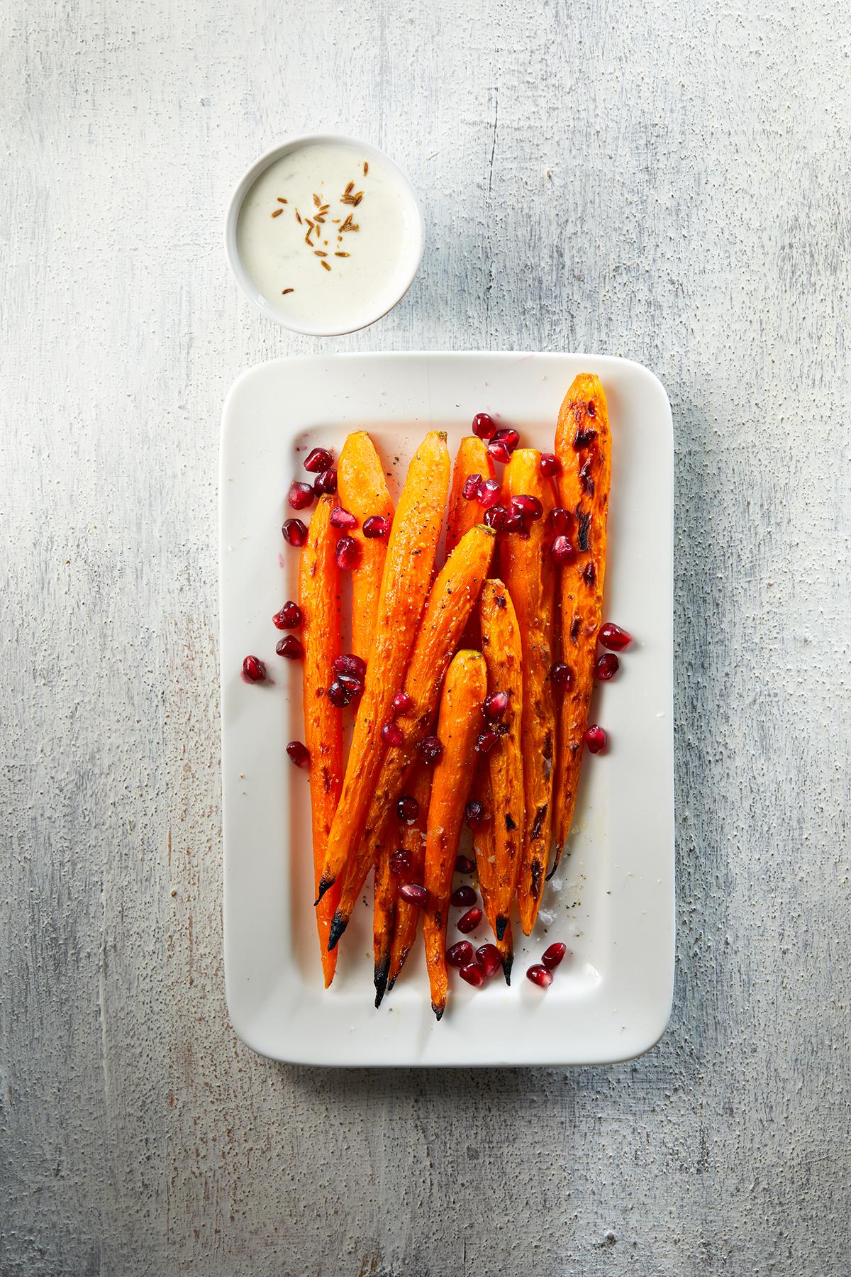 Geroosterde honingwortels met komijn-yoghurtsaus en granaatappel